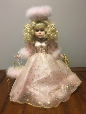 Value of a Porcelain Doll - doll wearing a fancy light pink dress with hat and curly blonde hair