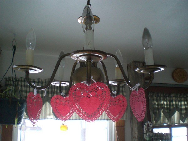 Heart Doily Valentine Decoration - red paper heart doilies hanging from light fixture