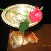 An antique silver dessert cup holding a red rose.