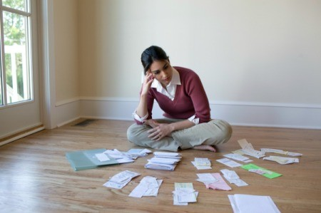 A woman looking at many receipts and paperwork on a wooden floor.