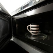 An open microwave oven, with a mug inside.