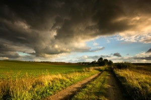 Storm clouds over green farmland with blue sky in the distance.