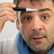 A man trimming between his eyebrows.