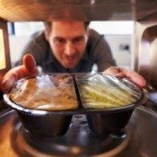 A man putting a frozen dinner in the microwave.