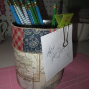 Decorate Food Cans For Office/ or Craft Storage - can decorated with scrapbook paper and wide ribbon holding pencils and a note half on with a clip