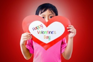 A boy holding a heart shaped Valentine card.