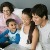 A family using a laptop computer on a couch.