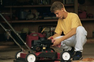 A teenager fixing a lawn mower.