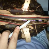 A candle being used to lubricate the zipper of a purse.