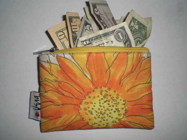 A orange and yellow flowered wallet with money sticking out the top.