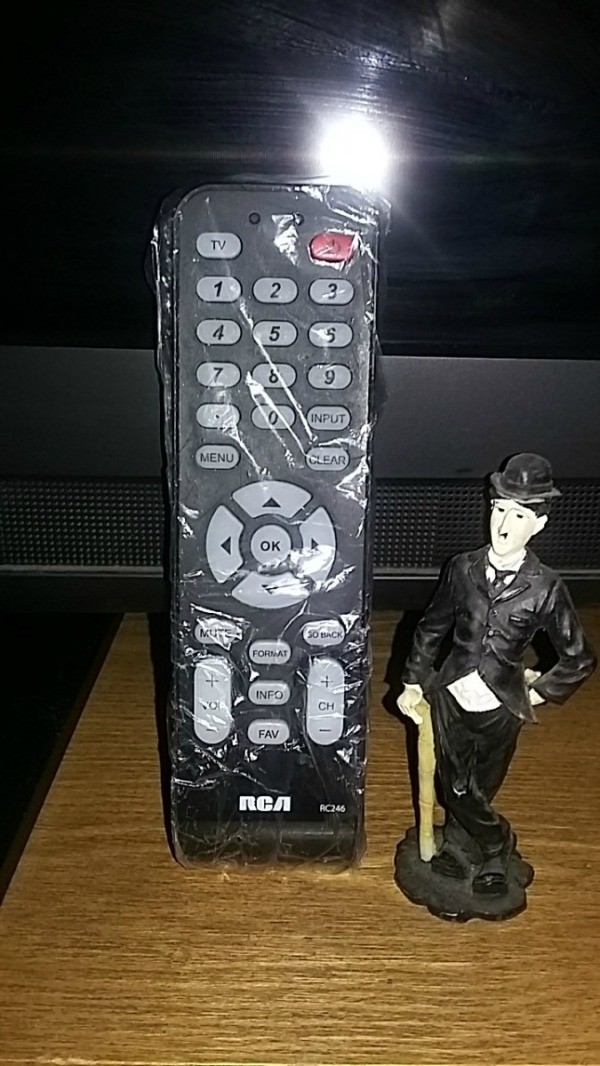 A television remote control covered in plastic wrap.