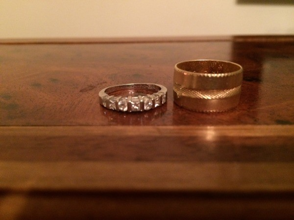 Wedding rings on a wooden dresser.