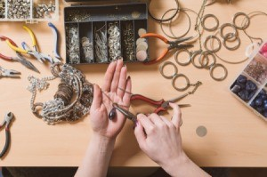 A person assembling jewelry on a craft table.