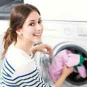 A woman pulling laundry out of a washing machine.