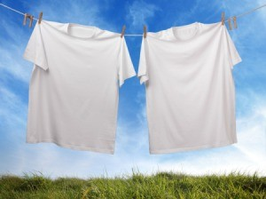 A sagging clothesline with two white t-shirts pinned on it.
