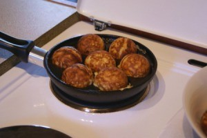 A Danish aebleskiver pan on a stove.