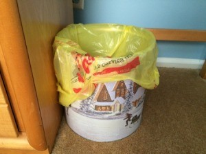 A popcorn tin being used as a trash can.
