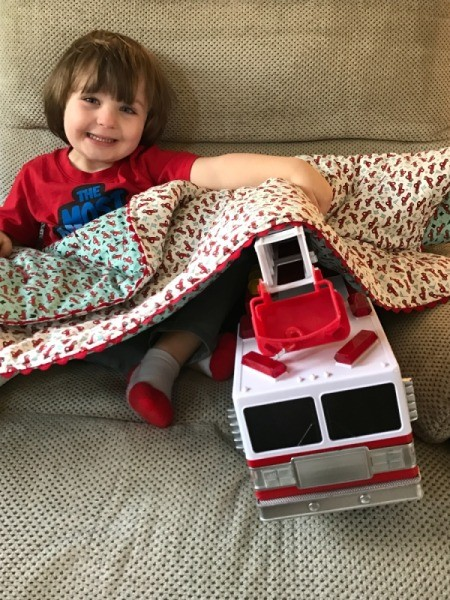 Whole Cloth Tied Quilt with Ric Rac Trim - toddle with large firetruck under the quilt