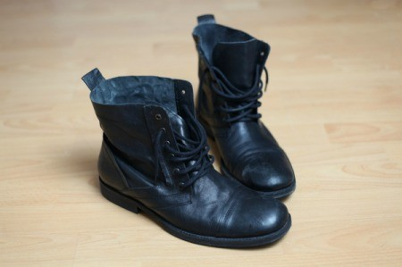 A pair of boots with black rubber soles on a wood floor. - Removing Scuff Marks From Hardwood Floors ThriftyFun
