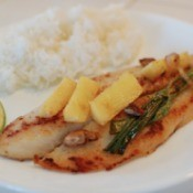 Pan Fried Tilapia with green onion and ginger chunks on plate
