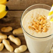 A smoothie in a glass with peanuts and bananas around.
