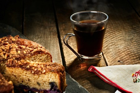 A plate of coffee cake with a cup of coffee on a table.