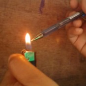 A ballpoint pen being heated in the flame of a pocket lighter.