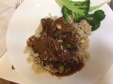 Mongolian Beef on rice with broccoli on plate