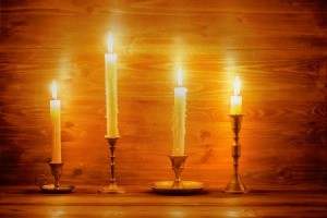 Four different candlesticks with white taper candles.