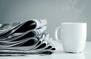 A stack of newspaper next to a cup of coffee.