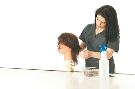 A student working on a hairstyle on a mannequin head.