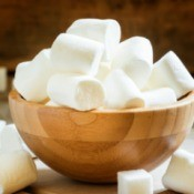 A bowl full of large white marshmallows.