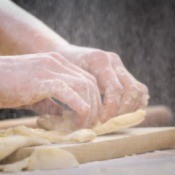 A woman making knots with dough.