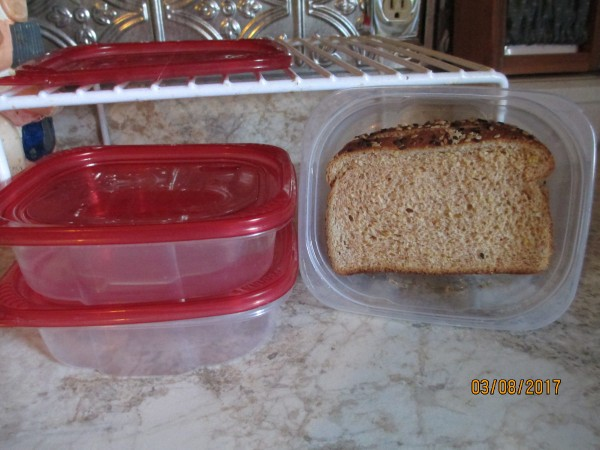 A reusable plastic container with a sandwich stored inside.