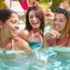 Three girls smiling in a pool.