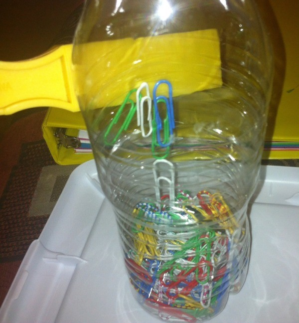 Magnetic Discovery Bottles - magnet against a bottle of paper clips