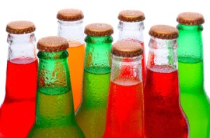 A bunch of brightly colored sodas in clear glass bottles.