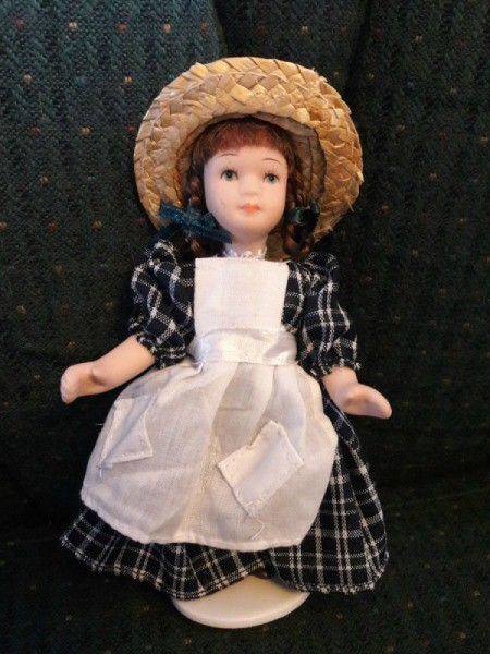 Doll Identification and Value - doll wearing straw hat and plaid dress with bib apron