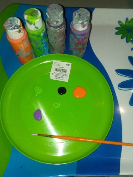 A frisbee being used as a paint palette.