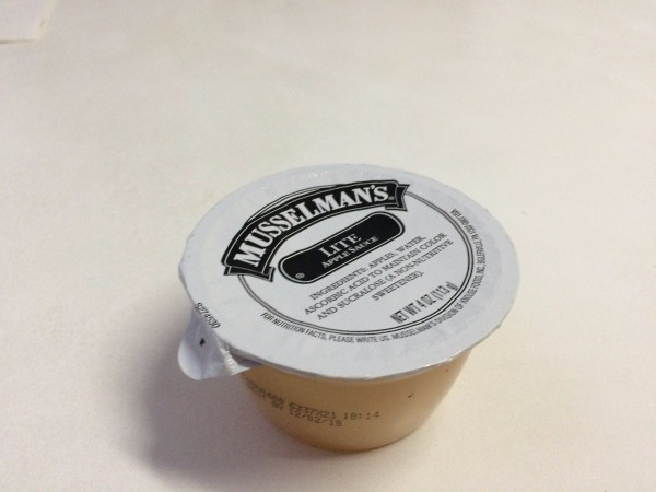 A small serving sized container of applesauce.
