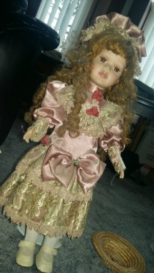 Information and Value of Porcelain Dolls - doll with long curly hair wearing a pink satin period dress with ecru lace at bottom