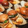 A row of beef sliders, with potato chips.