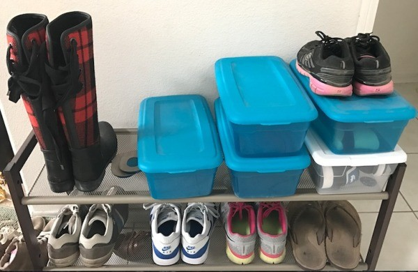 Shoes on a rack and in plastic shoe boxes.