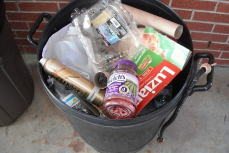 A trash can full of recycling.