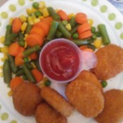 A plate of chicken nuggets with ketchup in a recycled scoop.