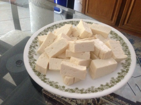 A plate of tofu, chopped into pieces.