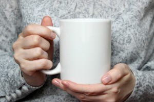A woman holding a blank coffee cup.