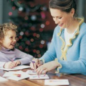 A woman and girl writing Christmas cards.
