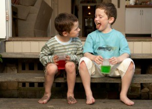 Two boys drinking koolaid outside.