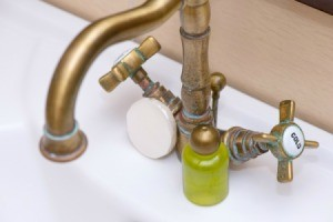 Antique faucet with green stains.